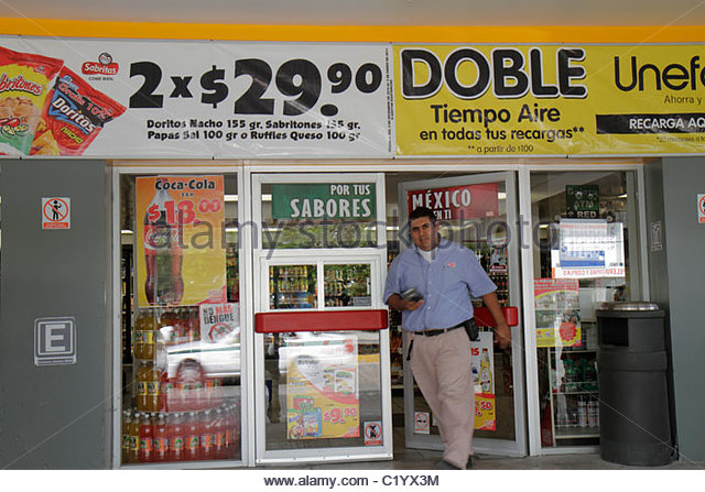 Cancun Mexico Yucatán Peninsula Quintana Roo Hispanic man Oxxo convenience store door exit banner promotion - Stock Image