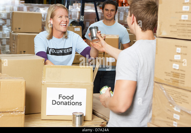 Volunteers Collecting Food Donations In Warehouse - Stock Image