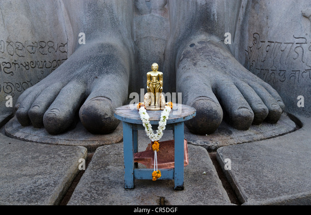 The small statue of Bahubali at the feet of the gigantic statue of Gomateshwara in Sravanabelagola, used for special - Stock Image