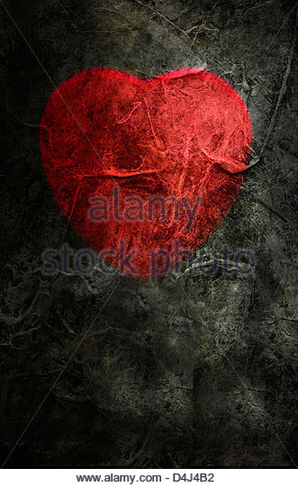 Red heart shape on grungy dark background - Stock Image
