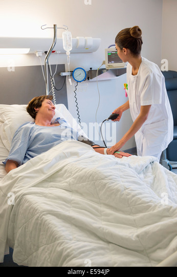 Female nurse checking patient's blood pressure on hospital bed - Stock Image