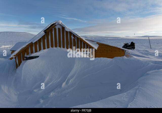 Dyranut Mountain Lodge, the highest on road R7, in Hardangervidda, buried in snow during the winter season. - Stock Image