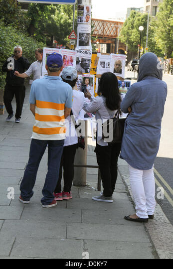 London, UK. 16th June 2017. A group of people stand by a board with missing person posters on 17 June. At least - Stock Image