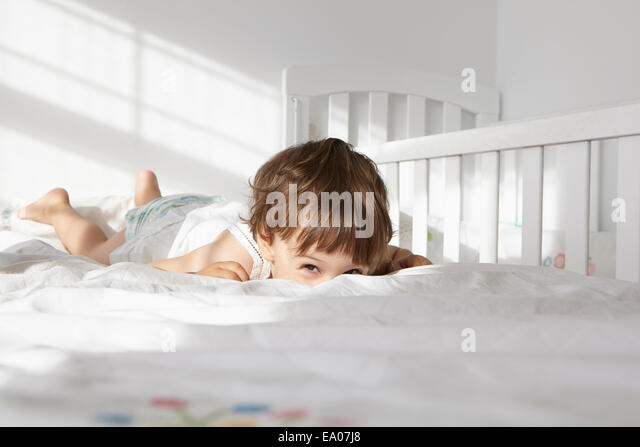 Candid portrait of female toddler peeking over bed quilt - Stock Image