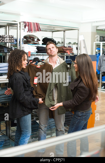 Man standing whilst women compare clothing options against him - Stock Image