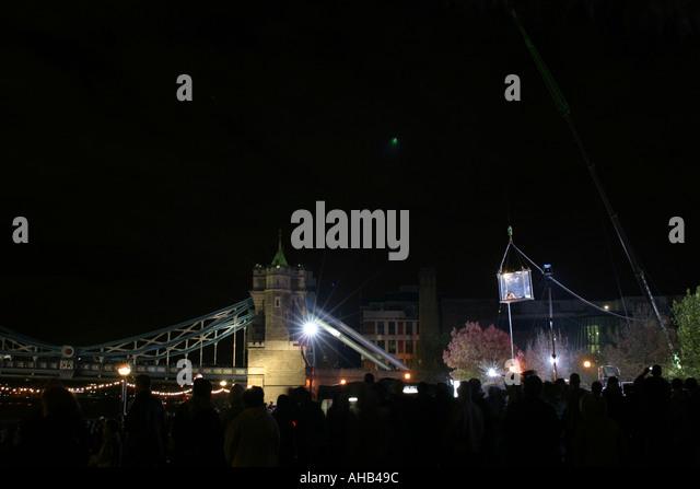 Crowd gathered around David Blane in his box at Tower Bridge at night - Stock Image