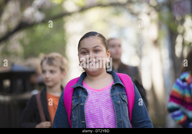 A group of children on the sidewalk with school bags or book bags - Stock Image