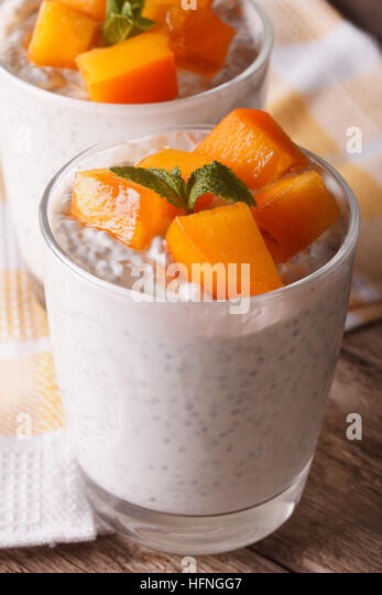 Yogurt with chia seeds and persimmon close-up on the table. vertical - Stock Image