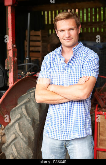 Portrait Of Farmer With Old Fashioned Tractor - Stock Image