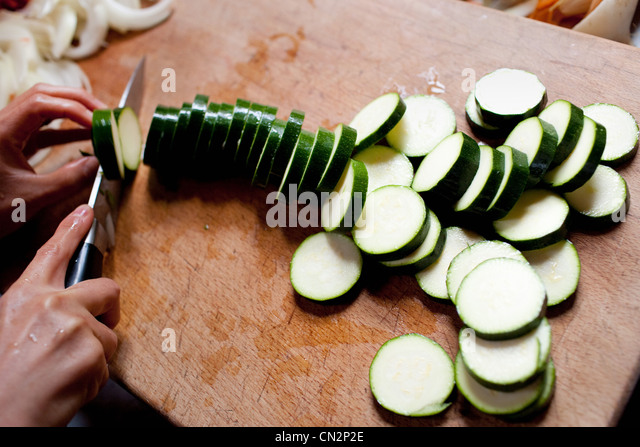 Person chopping courgette - Stock Image