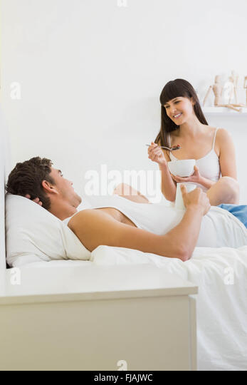 Young couple having breakfast on bed - Stock Image