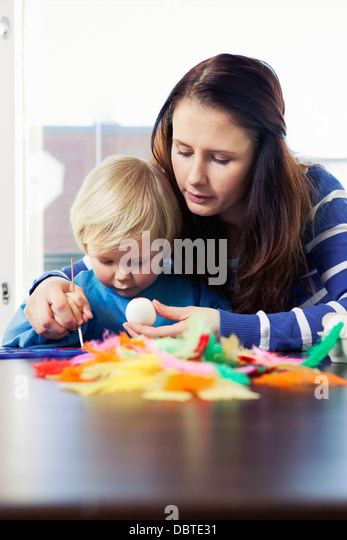 Mother helping daughter (2-3) with painting Easter egg - Stock Image