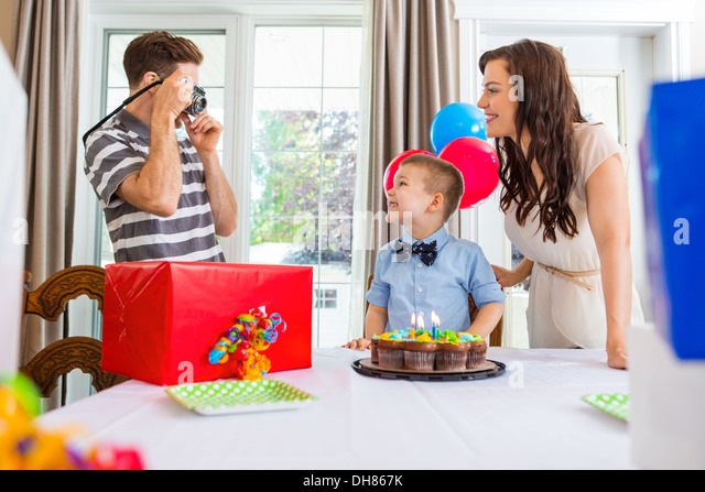 Father Taking Picture Of Birthday Boy And Woman - Stock Image