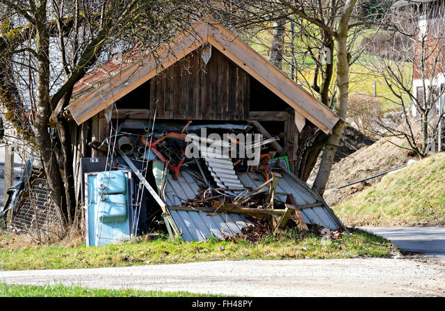 Old wooden shed overflowing with scrap metal, Chiemgau, Upper Bavaria, Germany, Europe - Stock Image