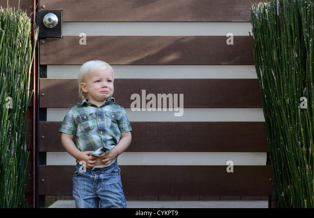 Toddler boy crying outdoors - Stock Image
