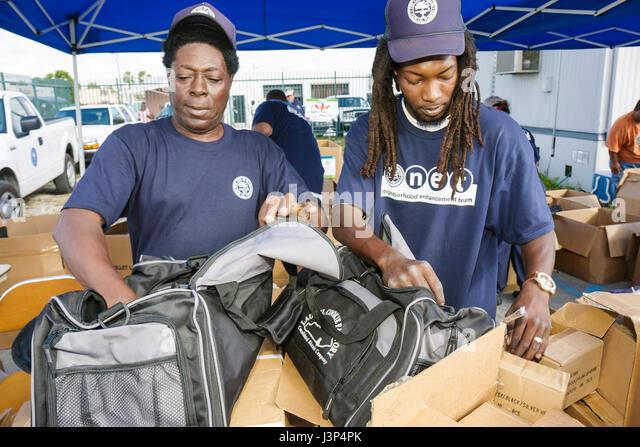 Miami Florida Little Haiti Thanksgiving Turkey Give-Away give away volunteers Black Haitian man men packing bags - Stock Image
