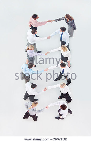 Business people in rows shaking hands face to face - Stock Image