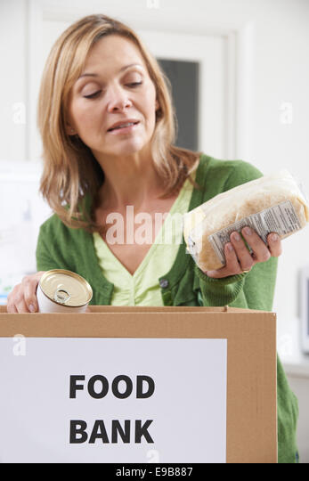Woman Making Donation To Food Bank - Stock Image