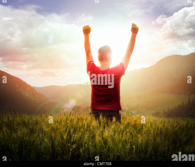Young man with arms raised looking at sunset with mountains ahead - Stock Image