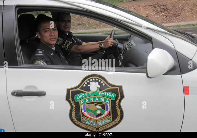 Panama City Panama Balboa National Police policeman officer patrol car public safety security shield Hispanic man - Stock Image