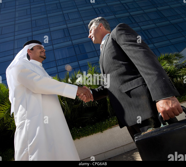 Arab businessman and western businessman shaking hands in front of office building. - Stock Image