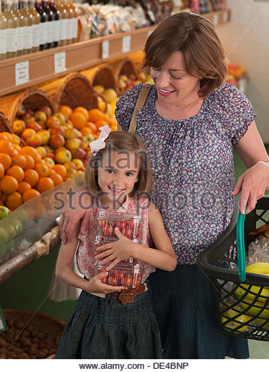 Mother and daughter shopping together in grocery store - Stock Image