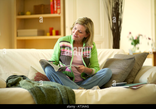 A woman sitting on a sofa looking through home shopping catalogues - Stock Image