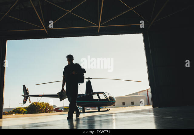 Silhouette of a pilot arriving at the airport with a helicopter in background. Helicopter pilot in airplane hangar. - Stock Image