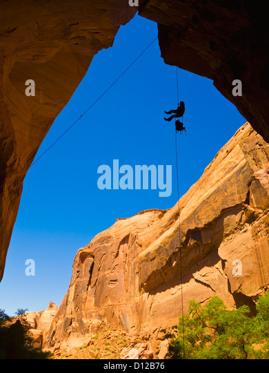 A Female Athlete Rappeling Down A Dry Utah Slot Canyon Waterfall; Hanksville Utah United States Of America - Stock Image