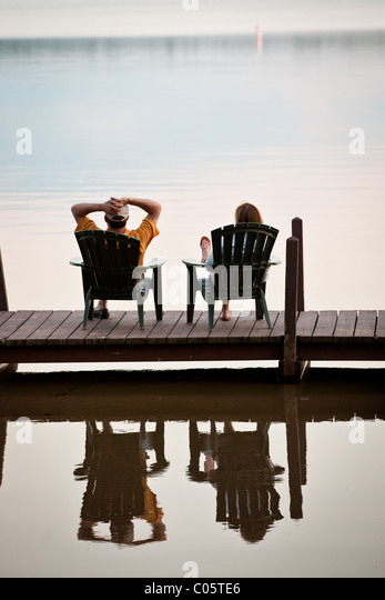 Couple watches the sunset on a lake in the Northwoods of Wisconsin. - Stock-Bilder