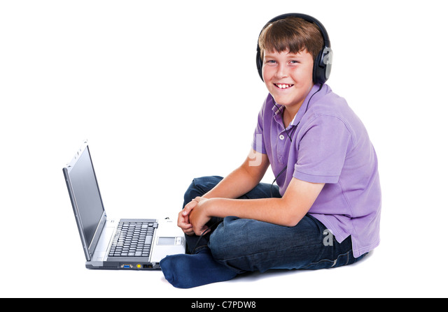 Photo of an 11 year old school boy wearing headphones sitting with a laptop computer, isolated on a white background. - Stock Image
