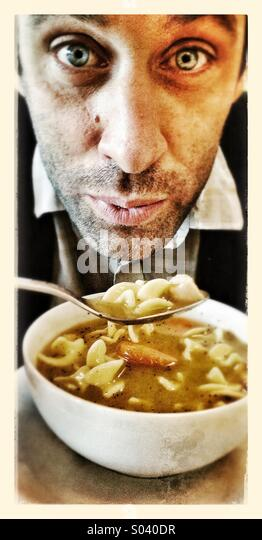 Guy eating soup - Stock Image