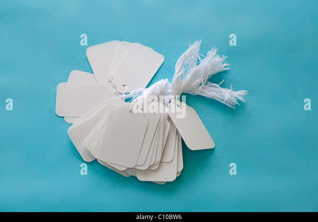 white blank price tags with string on blue surface - Stock Image