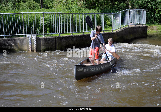 two teenage boys paddeling canadian canoe on fast flowing river - Stock Image