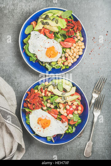Healthy breakfast with fried egg, chickpea sprouts, seeds, fresh vegetables and greens in blue bowls over grey concrete - Stock Image