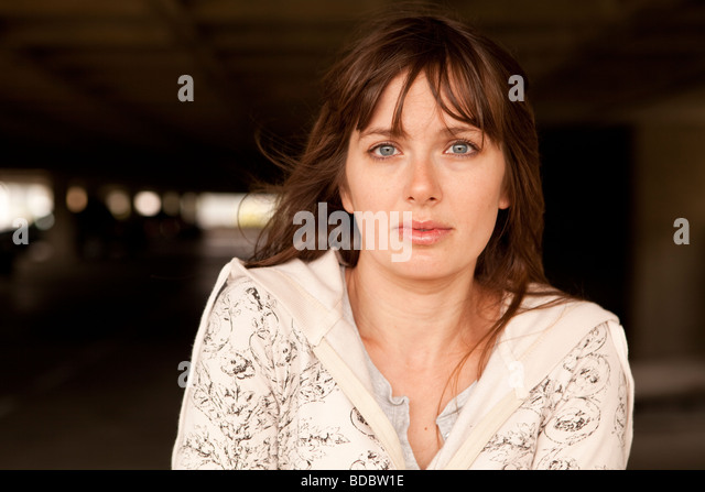 Portrait of Caucasian female brunette against waffle-like pattern of parking garage structure. - Stock Image