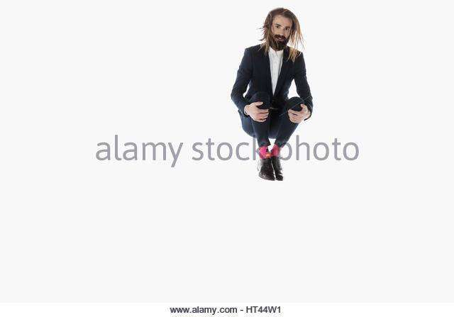 Portrait businessman jumping, hugging knees against white background - Stock-Bilder