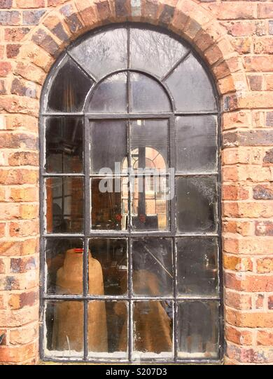 Old arched steel window, Crittal style, in an industrial workshop - Stock Image