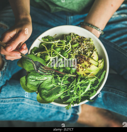 Green vegan breakfast meal in bowl with spinach, arugula, avocado, seeds and sprouts. Girl in jeans holding fork - Stock Image