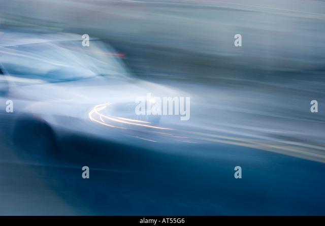 fast moving car, blurred camera pan, slow shutter speed camera technique, blue - Stock Image