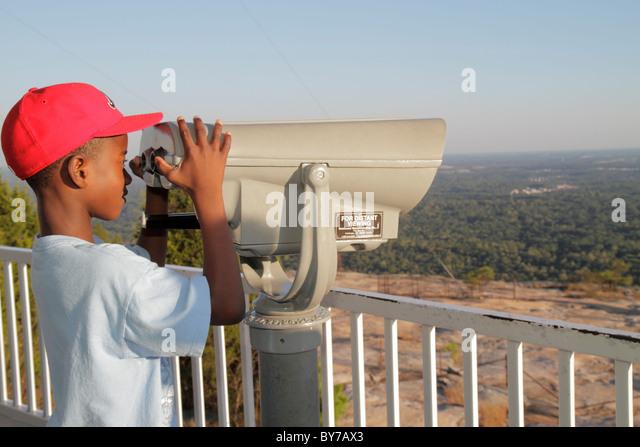 Atlanta Georgia Stone Mountain Park quartz monzonite monadnock geology summit Black boy child coin-operated binoculars - Stock Image