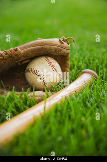 Baseball equipment laying on grass - Stock Image