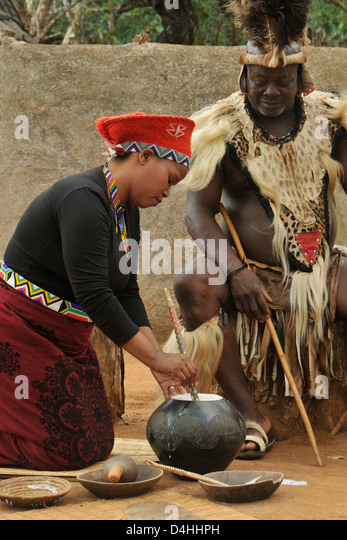 Zulu wife skimming foam off traditional beer Chief looking on Shakaland South Africa Cultures Travel ethnicity - Stock-Bilder