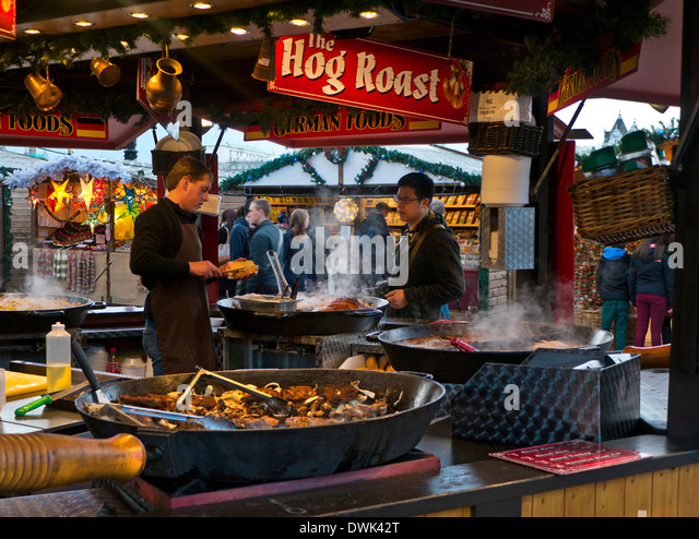 South Bank German Christmas market takeaway hog roast food stall and visitors London UK - Stock Image