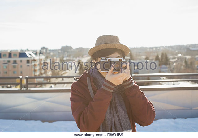 Young man photographing with vintage camera outdoors - Stock-Bilder
