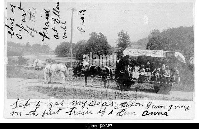 African Americans riding in wagon carried by four horses, on dirt pathway in middle of field with trees, 1915. - Stock Image