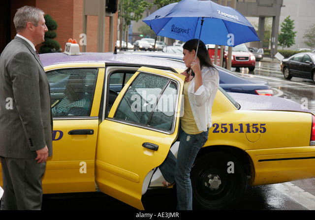 Ohio, Cincinnati, Hilton Netherland Plaza Hotel, woman enters taxi cab, umbrella, rain, doorman, - Stock Image