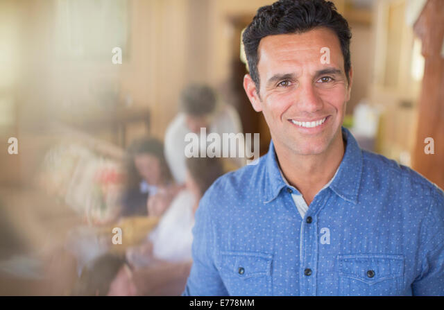 Man smiling with family near - Stock Image