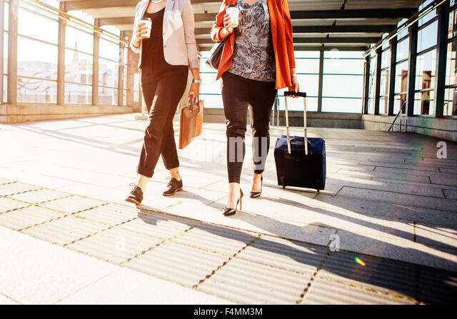 Low section of businesswomen with luggage walking at railroad station - Stock Image