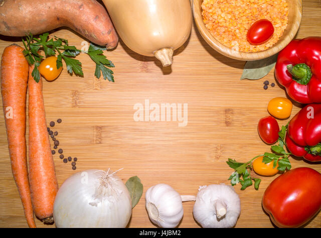 ingredients for lentil soup on a wooden board with copy space in the center - Stock Image